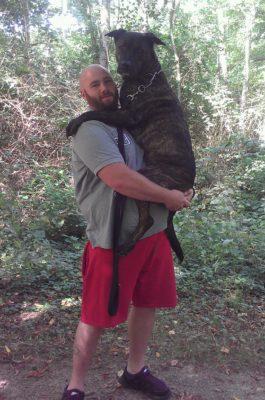 Mann trägt Hund